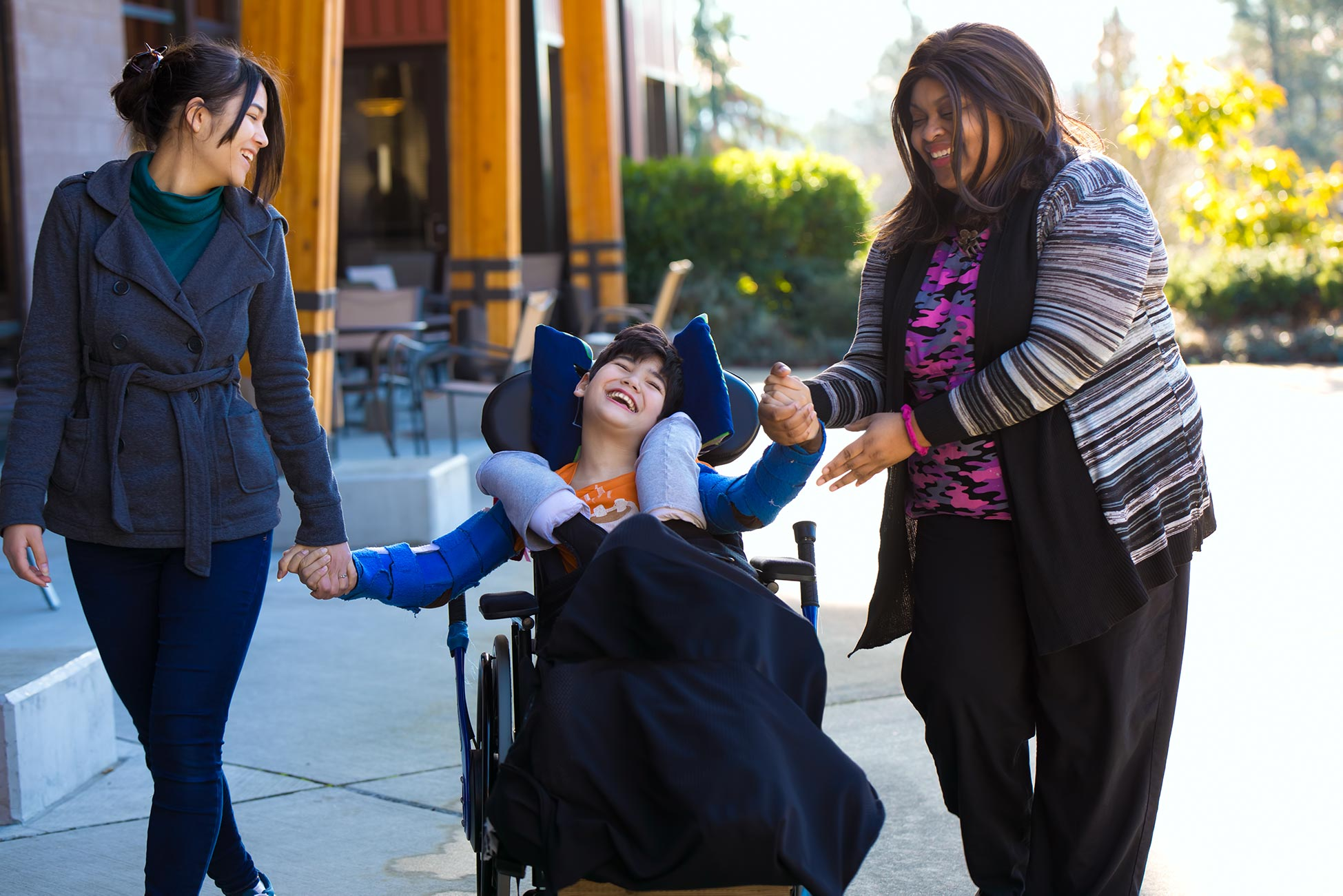 Carers laughing with disabled child
